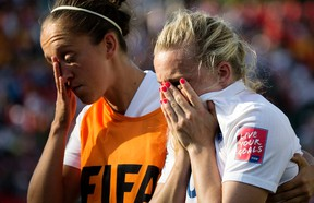 England's Josanne Potter (left) consoles Laura Bassett (right) following England's 2-1 loss to Japan during FIFA Women's World Cup semifinal action at Commonwealth Stadium in Edmonton on Wednesday, July 1, 2015. (David Bloom/Postmedia Network)