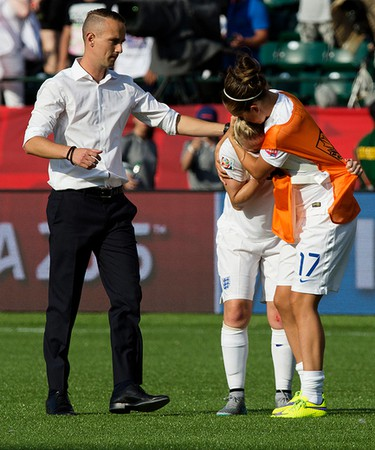 Coach Mark Sampson and England's Josanne Potter (17) console Laura Bassett (6) following England's 2-1 lose to Japan during FIFA Women's World Cup Canada 2015 action at Commonwealth Stadium, in Edmonton Alta. on Wednesday July 1, 2015. David Bloom/Edmonton Sun/Postmedia Network