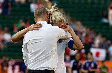 Coach Mark Sampson England's consoles Steph Houghton (5) following the team's 2-1 lose to Japan during FIFA Women's World Cup Canada 2015 action at Commonwealth Stadium, in Edmonton Alta. on Wednesday July 1, 2015. David Bloom/Edmonton Sun/Postmedia Network