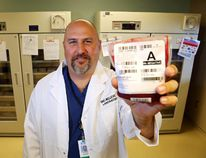 Luke Hendry/The Intelligencer Chief surgeon Dr. Sean McIlreath holds a unit of red blood cells in front of the Belleville General Hospital laboratory's