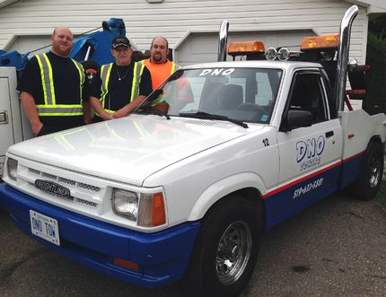 Corbin, left, Don and Cole Neville of DNO Towing proudly show off a long-lost piece of the company's history. The custom Mazda tow truck was built by the company's original owner Norm Dean in 1992 and recently bought by the Neville family.