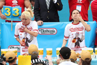 """Miki Sudo, left, and Sonya """"Black Widow"""" Thomas compete in Nathan's Famous Fourth of July International Hot Dog Eating Contest women's competition Saturday July 4, 2015 at Coney Island in the Brooklyn borough of New York. Sudo won the competition eating 38 hot dogs and buns in 10 minutes. Thomas came in second eating 31 hot dogs and buns in 10 minutes. (AP Photo/Tina Fineberg)"""