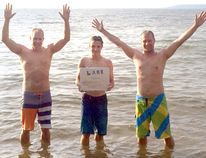 From left, Darren Atchison, Josh Atchison and Derek Atchison celebrate in Lake Superior a week ago, the last swim in their adventure to swim in all five Great Lakes in one day. (CONTRIBUTED PHOTO)