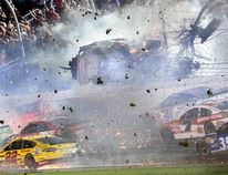 Austin Dillon (3) goes airborne and hits the catch fence as he was involved in a multi-car crash on the final lap of the NASCAR Sprint Cup series auto race at Daytona International Speedway, Monday, July 6, 2015, in Daytona Beach, Fla. (Stephen M. DoweLl/The Orlando Sentinel via AP)