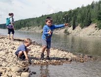 Brennan Munro, 4 (right) and his brother Daniel, 2, throw rocks into the Wapiti River on Sunday July 5, 2015 in O'Brien Provincial Park, as mom Leanne Brunidge watches. Although temperatures were not as high as last weekend, plenty of people were out at O'Brien enjoying the good weather and cool water with their families. Devyn Ens/Grande Prairie Daily Herald-Tribune/Postmedia Network