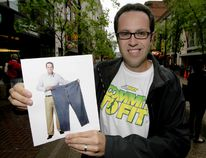Jared Fogle, the Subway restaurant poster boy who lost 245 pounds on a Subway diet, mugs with a photo of his former self in Calgary, Alta., in this June 15, 2011 file photo. (LYLE ASPINALL/CALGARY SUN/Postmedia Network)