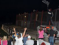 Tyler Reynolds waves the checkered flag standing atop his ride in the new'victory lane' established at the Brockville Ontario Speedway. Reynolds won the sportsman rookie feature race Saturday. (NICK GARDINER/The Recorder and Times)