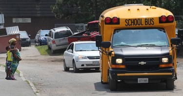 A mother waits for her child to get off the bus at the Albion-Heatherington community in Ottawa Tuesday July 7, 2015. The city of Ottawa is trying to decide which city community should receive funding for projects.  Tony Caldwell/Ottawa Sun/Postmedia Network