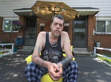 Peter Warner sits outside his home in the Albion-Heatherington community in Ottawa Tuesday July 7, 2015. The city of Ottawa is trying to decide which city community should receive funding for projects. Peter would like politicians to follow through with any commitments they make to improve their community.  Tony Caldwell/Ottawa Sun/Postmedia Network