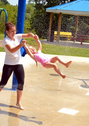 Erin Cronin swings Larissa Seliske through the spray at the West Perth Splash Pad on a hot Friday afternoon July 10. GALEN SIMMONS/MITCHELL ADVOCATE