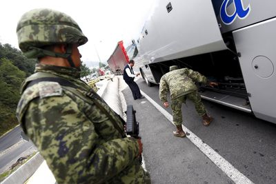 "Soldiers inspect a bus at a checkpoint on an access highway to Mexico City, July 12, 2015. Mexico's most notorious drug lord, Joaquin ""El Chapo"" Guzman, broke out of a high security prison on Saturday night for the second time, escaping in a tunnel built right under his cell, and heaping embarrassment on President Enrique Pena Nieto. (REUTERS/Edgard Garrido)"