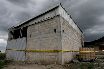 A police cordon is seen at a warehouse where a tunnel, connected to the Altiplano Federal Penitentiary and used by drug lord Joaquin 'El Chapo' Guzman to escape, was located in Almoloya de Juarez, on the outskirts of Mexico City, July 12, 2015. (REUTERS/Tomas Bravo)
