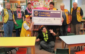 Representatives from the Cochrane Lions Club, Library staff and patrons gather to acknowledge the service club's contribution to the summer reading program.