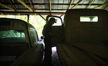 """Maintenance man Rockey Bryson looks at a 1946 Ford truck used in the movie """"Murder in Coweta County"""" starring Johnny Cash and Andy Griffith as it sits at Old Car City, the world's largest known classic car junkyard Thursday, July 16, 2015, in White, Ga. �There�s a lot of them sitting back here I don�t want to see going to rust,"""" Bryson said. """"It�s kind of sad to see them. There�s a lot of history here."""" (AP Photo/David Goldman)"""
