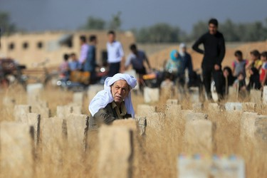A man sits amidst graves as people visit a cemetery, on the first day of the Muslim holiday of Eid al-Fitr, which marks the end of the holy month of Ramadan, in the Douma neighborhood of Damascus, Syria July 17, 2015. REUTERS/Bassam Khabieh