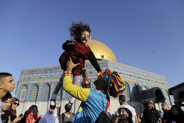 A man dressed as a clown plays with a Palestinian girl on the first day of the Muslim holiday of Eid al-Fitr, which marks the end of the holy month of Ramadan, near the Dome of the Rock at the compound known to Muslims as the Noble Sanctuary and to Jews as Temple Mount, in Jerusalem's Old City, July 17, 2015. REUTERS/Ammar Awad