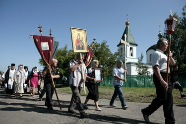 People take part in a procession to attend a commemoration ceremony near the site of the Malaysia Airlines flight MH17 plane crash in the village of Hrabove in Donetsk region, Ukraine, July 17, 2015. The rebel-held east Ukrainian village where a Malaysian airliner was shot down honored the 298 victims at a simple ceremony on Friday as calls grew for an international tribunal to prosecute those who brought it down. After a church service in the village of Hrabove, residents joined a procession across an open field to a gravestone placed near the charred area where twisted metal and body parts came crashing down on July 17 last year. REUTERS/Kazbek Basaev