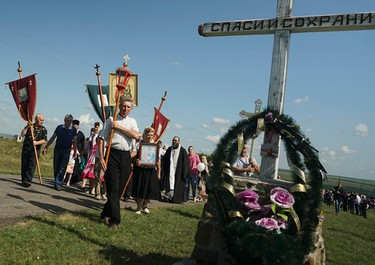"""A religious procession passes an Orthodox cross with a sign reading Save and Guard at the crash site of the Malaysia Airlines Flight 17, near the village of Hrabove, eastern Ukraine, Friday, July 17, 2015. Residents of the Ukrainian village where the Malaysian airliner was shot down with 298 people aboard a year ago began a procession to the crash site on Friday, while the Australian prime minister remembered the """"savagery"""" of the disaster by unveiling a plaque in Canberra that's set in soil from the place where the plane went down. (AP Photo/Mstyslav Chernov)"""