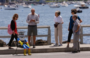 Area residents gather around HitchBOT, a hitchhiking robot, as it waits for its first ride Friday, July 17, 2015, in Marblehead, Mass. HitchBOT is beginning its' first cross-country hitchhiking trip of the U.S., in Marblehead with a final destination goal of reaching San Francisco. (AP Photo/Stephan Savoia)