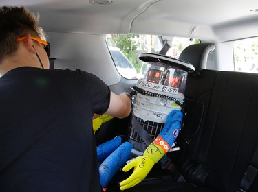 German tourist Eric Vogel straps a seatbelt around HitchBOT, a hitchhiking robot, as Vogel and his traveling companions give hitchBot its first ride Friday, July 17, 2015, in Marblehead, Mass. HitchBOT is beginning its' first cross-country hitchhiking trip of the U.S., in Marblehead with a final destination goal of reaching San Francisco. (AP Photo/Stephan Savoia)
