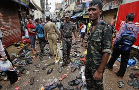 Indian policemen stand at the site near a woman who fainted during a stampede at the annual Rath Yatra or Lord Jagannath chariot procession in Puri, 65 kilometers (40 miles) from the eastern Indian city of Bhubaneswar, India, Saturday, July 18, 2015. Police say the crowd swelled and surged toward a chariot being carried in a procession that caused the stampede, according to PTI. (AP Photo/Biswaranjan Rout)