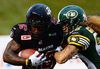 Ottawa Redblacks' Chevon Walker is tackled by Edmonton Eskimos' Aaron Grymes during first quarter CFL football action on Friday, July 17, 2015.  THE CANADIAN PRESS/Sean Kilpatrick