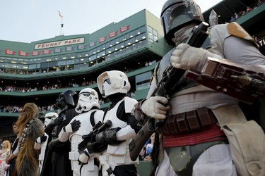 People dressed as Star Wars characters from the 501st New England Garrison stand for the U.S. National Anthem before the MLB baseball game between the Tampa Bay Rays and the Boston Red Sox at Fenway Park in Boston, Massachusetts, United States May 4, 2015.  REUTERS/Brian Snyder