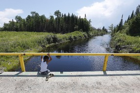 A boy from the Shoal Lake 40 First Nation sits on a bridge over a channel two summers ago. (THE CANADIAN PRESS/John Woods file photo)