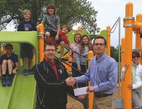 Ralph Hamm of the Curtis Klassen Memorial Fund (CKMF) presents a cheque for $2,000 to Ecole West Park School Playground Project. Receiving the cheque are Principal Alan Jones (left) and several West Park School students. (SUPPLIED PHOTO)