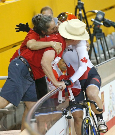 Monique Sullivan stops to hug parents trackside after winning the gold medal in women's sprints cycling at the Pan Am Games velodrome on Saturday July 18, 2015.(MICHAEL PEAKE/Toronto Sun)