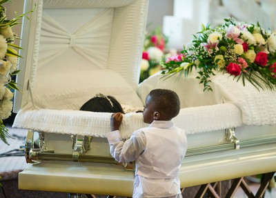 A young mourner pays his respects at the funeral for Lecent Ross, 14, at Abundant Life Assembly church in Toronto, Ont. on Saturday July 25, 2015. (Ernest Doroszuk/Toronto Sun)
