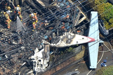 The wreckage of a plane is seen at a crash site in the suburbs of Tokyo, Sunday, July 26, 2015. (Kyodo News via AP)