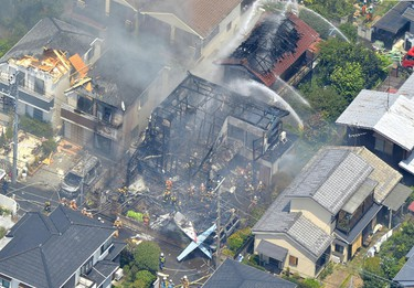 An aerial view shows debris of a crashed light plane (bottom C) and burning houses are seen after the plane went down in a residential area and burst into flames, in Chofu, outskirt of Tokyo, in this photo taken by Kyodo July 26, 2015.  REUTERS/Kyodo