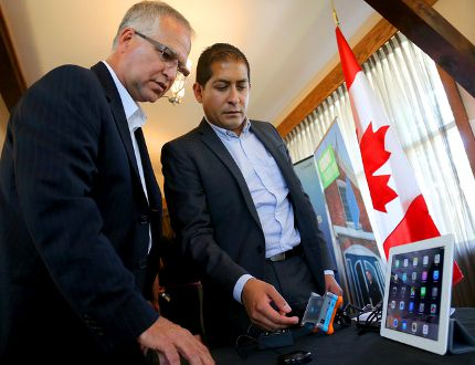 EMILY MOUNTNEY-LESSARD/THE INTELLIGENCER FedDev Minister Gary Goodyear learns about Tecla, hardware and software tools aimed at making touch screen devices easier to use for people with disabilities. At right is Mauricio Mezza, CEO of Komodo OpenLab, the parent company of Tecla. They are shown here during Monday's federal government funding announcement in Prince Edward County.