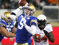 BC Lions defensive end Khreem Smith closes in on Bombers quarterback Drew Willy during a 2014 game in Winnipeg. Willy is questionable with a knee injury for Thursday's game against BC. POSTMEDIA NETWORK