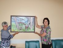 Brenda Cornwell (left) and Jackie Van Camp hang the new piece of artwork int eh lounge at Melfort Hospital.