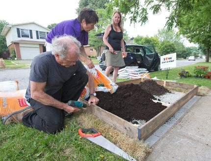 "Ron Benner, Stephanie Kelly and Wendy Goldsmith engage in some ""guerrilla gardening"" by building a flower bed on top of a concrete slap intended to hold a community mailbox in London. (DEREK RUTTAN, The London Free Press)"