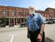 John Kerr, of Architectural Conservancy of Ontario Meaford, stands in front of a row of four heritage brick buildings on the east side of Meaford's main street last summer. His Ontario Municipal Board appeal of  conditional municipal approvals to build a five-storey condominium and knock the old buildings down resolved Thursday before a hearing. (James Masters/Owen Sound Sun Times)