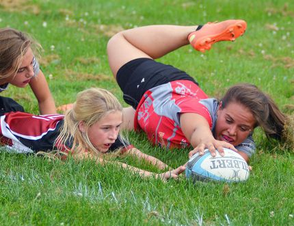Norfolk Harvesters' Mary Freeman scores a try while fellow teammate Josie Lopes (temporarily playing for the Guelph Redcoats) during a junior women's rugby game Wednesday night in Waterford. Norfolk defeated Guelph 20-0. (EDDIE CHAU Simcoe Reformer)