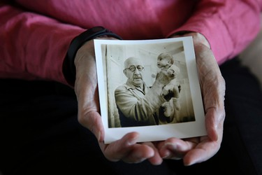 In this photo taken Thursday, July 23, 2015, Beth Allen holds a photograph taken by her father that shows her being held by Dr. Martin Couney at his Coney Island incubator sideshow, where she was on display with others after she was born premature in 1941, at her home in Hackensack, N.J. (AP Photo/Mel Evans)