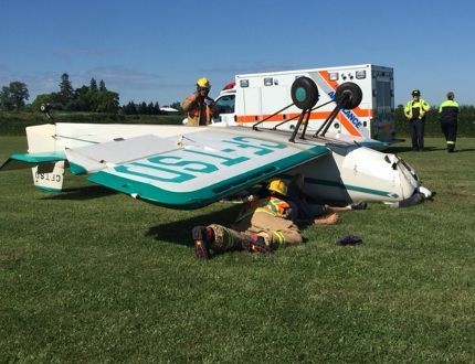 Firefighters are seen helping a pilot who's plane flipped while landing at Skyview Airport in Reece's Corners Friday, a witness says. The pilot appeared OK, the witness said. Handout/Sarnia Observer/Postmedia Network