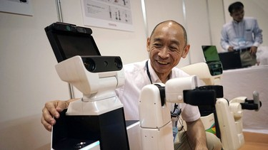 """In this July 24, 2015 photo, Toyota's engineer Kouichi Ikeda looks at new HSR, left, short for """"human support robot,"""" at a welfare and nursing exposition in Yokohama, south of Tokyo.(AP Photo/Eugene Hoshiko)"""