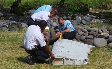 French gendarmes and police inspect a large piece of plane debris which was found on the beach in Saint-Andre, on the French Indian Ocean island of La Reunion, July 29, 2015. France's BEA air crash investigation agency said it was examining the debris,  in coordination with Malaysian and Australian authorities, to determine whether it came from Malaysia Airlines Flight MH370, which vanished last year in one of the biggest mysteries in aviation history. Picture taken July 29, 2015.     REUTERS/Zinfos974/Prisca Bigot