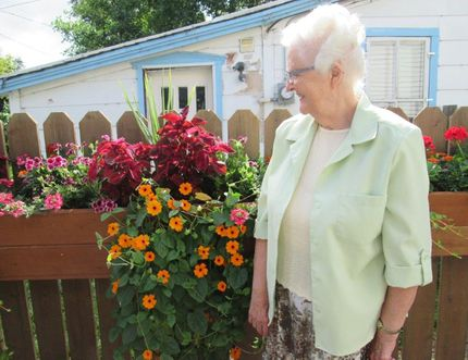 Co-host Jean Stanley glances at her floral planter box mounted to the fence, thoughtfully filled with aesthetically attractive floral plants. (submitted photo/Ted Meseyton)