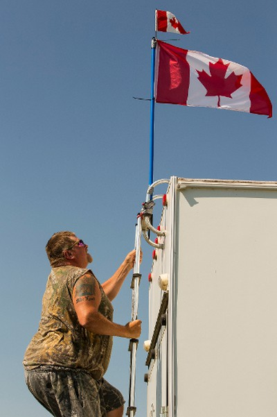 Shaun McLeod from Plamondon, Alta., takes his Canadian flag down off his trailer as he packs up in the campground after Big Valley Jamboree 2015 in Camrose, Alta. on Monday August 3, 2015. Ian Kucerak/Edmonton Sun/Postmedia Network