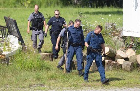 London Police officers search for evidence in a yard behind Sammy's Souvlaki on Trafalgar Street, where founder Sotirios (Sammy) Cardabikis and another unidentified man were injured in an early Sunday morning robbery, in London, Ont. on Monday August 3, 2015. Police are searching for multiple suspects. Craig Glover/The London Free Press/Postmedia Network