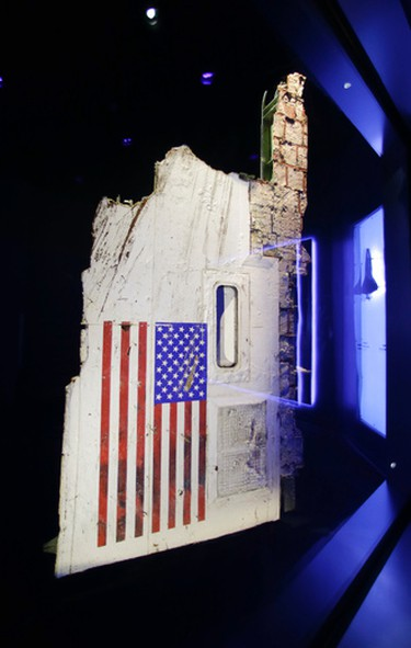 """In this Tuesday, July 21, 2015, photo, the left side body panel of space shuttle Challenger is displayed in a glass case at  the """"Forever Remembered"""" exhibit at the Kennedy Space Center Visitor Complex in Cape Canaveral, Fla. Challenger's wreckage _ all 118 tons of it, salvaged from the Atlantic _ was buried in a pair of former missile silos, 90 feet deep. The chamber containing this particular fuselage section had never been opened _ until the exhibit began to take shape. (AP Photo/John Raoux)"""