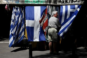 A man stands next to Greek national flag at a kiosk in central Athens, Greece, July 20, 2015. (REUTERS/Yiannis Kourtoglou)