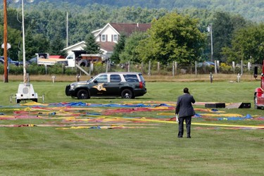 Investigators inspect the site of a circus tent that collapsed during a show Monday by the Walker Brothers International Circus at the Lancaster Fair grounds in Lancaster, N.H., Tuesday Aug. 4, 2015. A quick moving storm with 60 mph winds hit the tent shortly after the show started killing a father and daughter.(AP Photo/Jim Cole)