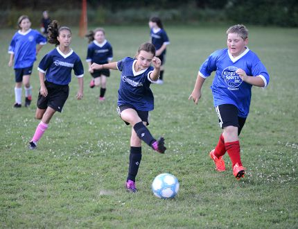 Ryan Paulsen / Daily Observer Heidi Hugli, centre, 10, advances past defender Bryce Haahs, right, during the final evening of soccer at Shady Nook Recreation Centre on Wednesday night, July 29.